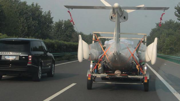 发现前方小轿车正牵引一架小型飞机